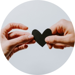 Two people's hands holding a heart
