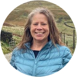 Photo of Michelle Every, Michelle smiling. She is standing with moorland behind her. her long hair down to her shoulders. She's wearing a teal padded jacket.
