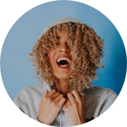 Photo of woman with light Brown skin and blond curly hair laughing. She's wearing a white hoody.